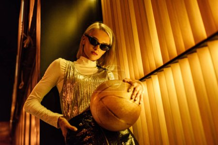bottom view of young woman in sunglasses with golden glossy basketball ball on street at night under yellow light