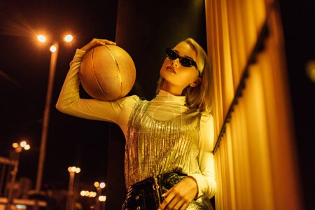 bottom view of beautiful woman in sunglasses with golden glossy basketball ball on street at night under yellow light
