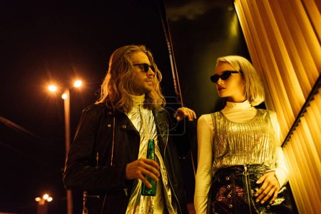 young attractive couple in stylish clothes and sunglasses flirting on night street under yellow light