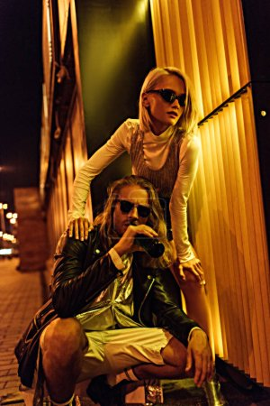 young stylish couple in fashionable clothes on night street under yellow light