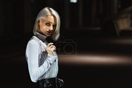 Photo for Young woman looking at camera on street at night under lantern light - Royalty Free Image