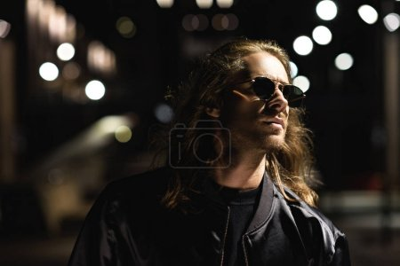 close-up portrait of attractive young man in sunglasses and leather jacket on city street at night
