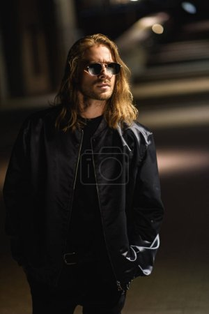 Photo for Attractive young man in sunglasses and leather jacket on city street at night - Royalty Free Image