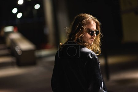 stylish young man in sunglasses and leather jacket on street at night