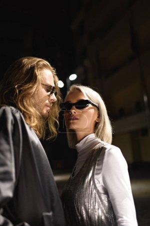 Photo pour Jeune couple à la mode en lunettes de soleil flirtant dans la rue la nuit - image libre de droit
