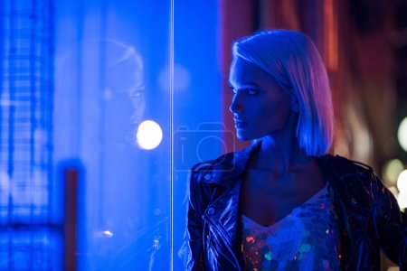 Photo for Stylish young woman in glossy tank top and leather jacket on street at night under blue light - Royalty Free Image