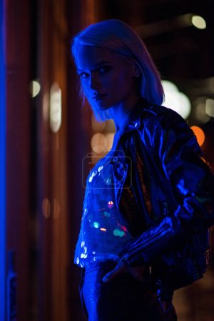 Photo for Attractive young woman in glossy tank top and leather jacket on street at night under blue light - Royalty Free Image