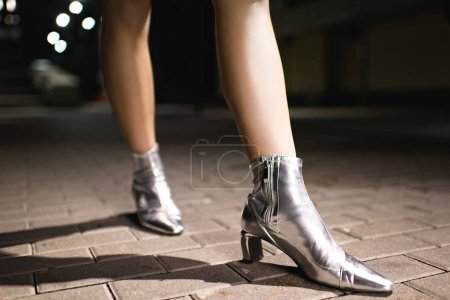 cropped shot of woman in glossy silver boots walking on street at night