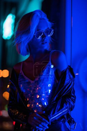Photo for Beautiful young woman in glossy tank top and sunglasses on street at night under blue light - Royalty Free Image