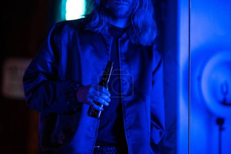 cropped shot of young man with bottle of beer under blue light on street at night