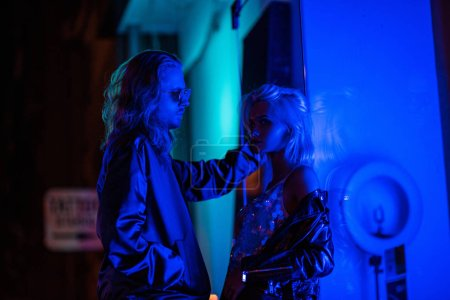 young stylish couple flirting under blue light on night street