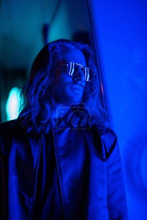 attractive young man in sunglasses under blue light on street at night