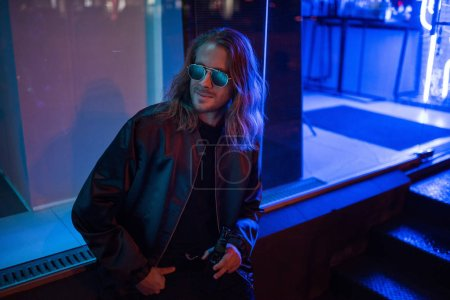 Photo for Attractive young man in leather jacket and sunglasses with bottle of beer on street at night under blue light - Royalty Free Image