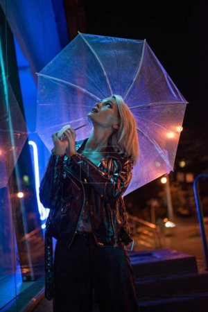 Photo for Beautiful young woman with umbrella looking up on street at night under blue light - Royalty Free Image