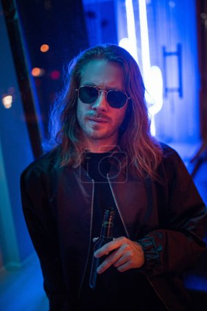 Photo for Handsome young man in leather jacket and sunglasses with bottle of beer on street at night under blue light - Royalty Free Image