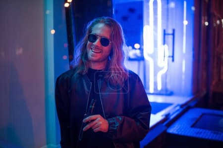 happy young man in leather jacket and sunglasses with bottle of beer on street at night under blue light