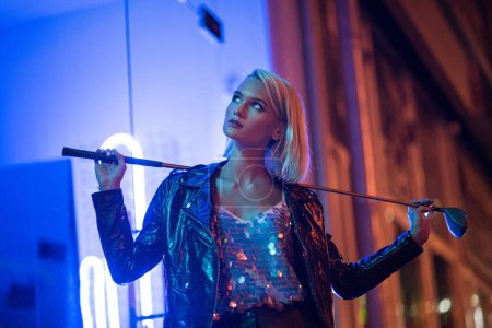 attractive young woman in leather jacket standing on street at night under blue light and holding golf club