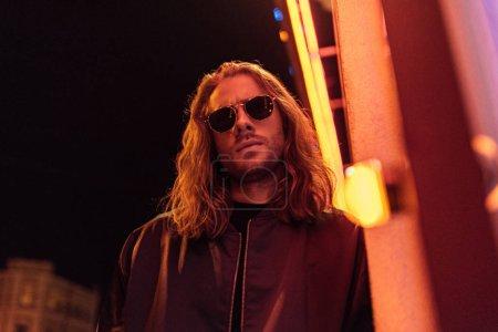 Photo pour Vue du bas de beau jeune homme en veste en cuir et lunettes de soleil dans la rue la nuit sous la lumière jaune - image libre de droit