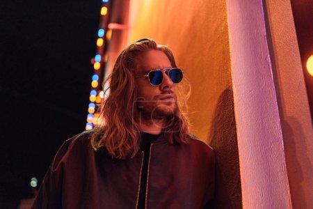 Photo pour Attrayant jeune homme en veste en cuir et lunettes de soleil dans la rue la nuit sous la lumière jaune - image libre de droit