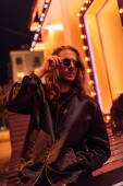 handsome young man in leather jacket and sunglasses spending time alone on street at night under yellow light