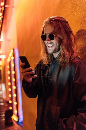 happy young man in leather jacket and sunglasses using smartphone on street at night under yellow light