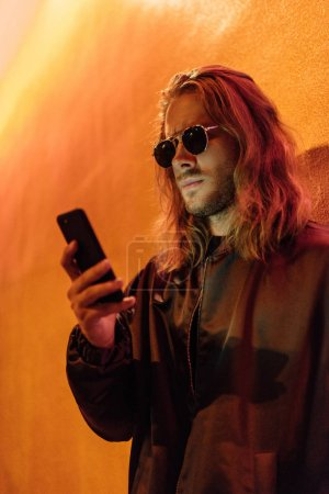 serious young man in leather jacket and sunglasses using smartphone on street at night under yellow light