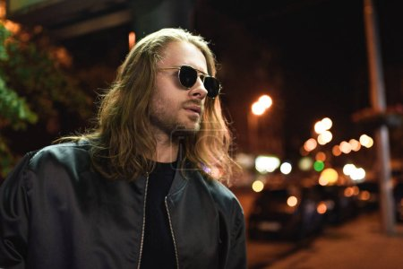 handsome young man in leather jacket and sunglasses on street at night