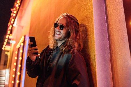 Photo pour Jeune homme riant veste en cuir et lunettes de soleil en utilisant smartphone dans la rue la nuit sous la lumière jaune - image libre de droit