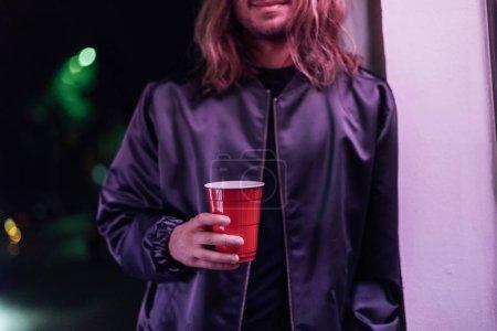 Photo pour Plan recadré de jeune homme avec tasse de boisson en plastique rouge dans la rue la nuit sous la lumière rose - image libre de droit