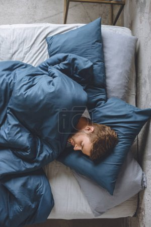 top view of young handsome man sleeping under blanket in his bed at home
