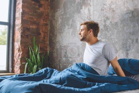 Photo pour Beau jeune homme se réveillant dans son lit le matin à la maison - image libre de droit