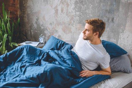 Foto de Seguro joven despierta en su cama durante el tiempo de mañana en casa - Imagen libre de derechos