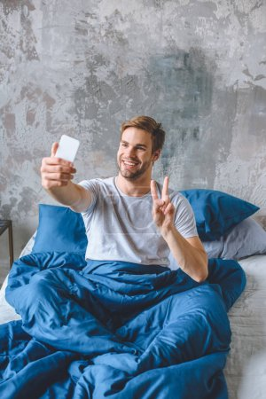 happy young man doing peace sign and taking selfie on smartphone in bed at home