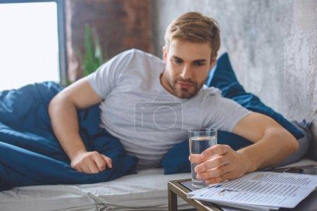 Selektywny fokus młody mężczyzna w łóżku biorąc szklankę wody w domu