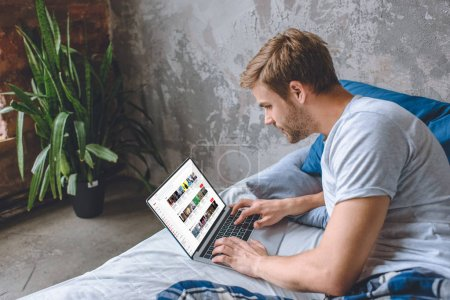Photo for Handsome young man in bed using laptop with youtube on screen - Royalty Free Image