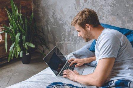 Photo pour Beau jeune homme au lit à l'aide d'un ordinateur portable avec site de réservation à l'écran - image libre de droit