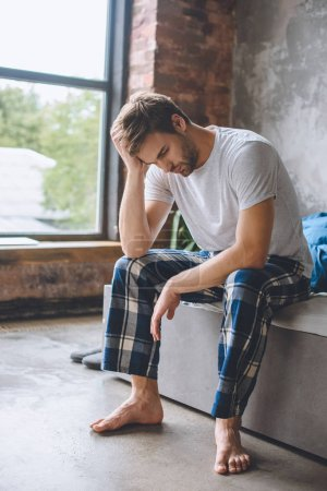 Photo for Tired young man just wake up and sitting on bed during morning time at home - Royalty Free Image