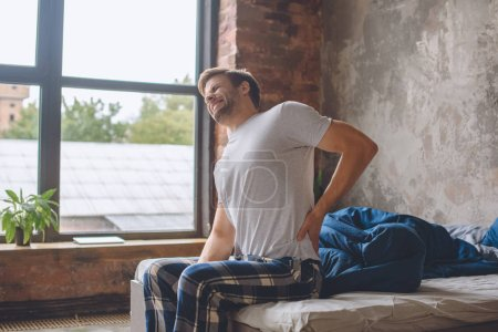 young man with pain in spine just wake up and sitting on bed at home