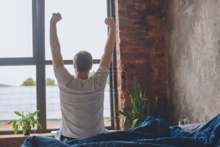 Photo for Rear view of young man sitting on bed with raised arms during morning time at home - Royalty Free Image