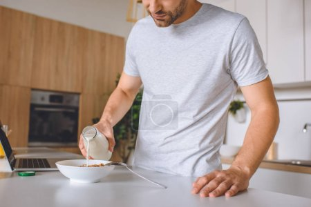 cropped image of man pouring milk into plate with flakes at kitchen table with laptop