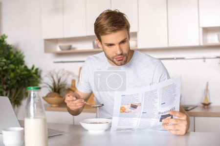 handsome young man eating flakes on breakfast and reading newspaper