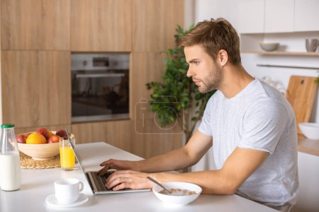 focused young man using laptop at kitchen table with breakfast