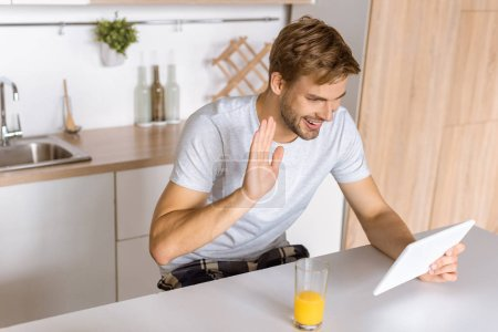 smiling young man waving by and and talking by digital tablet at kitchen
