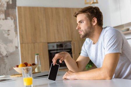 gentil jeune homme avec smartphone assis à la table de la cuisine avec le verre de jus
