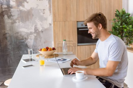 smiling young man using laptop at kitchen table with digital devices and coffee cup