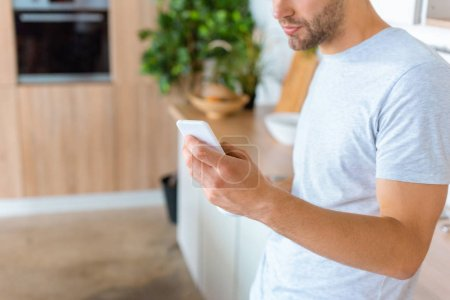 abgeschnittenes Bild eines Mannes mit Smartphone in der Küche