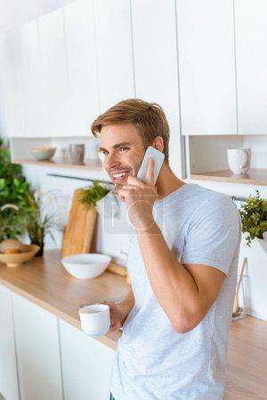 Lächelnder junger Mann mit Kaffee und Smartphone in der Küche