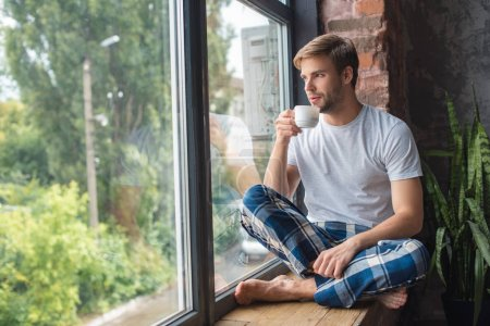serious young man sitting on windowsill and drinking coffee during morning time at home