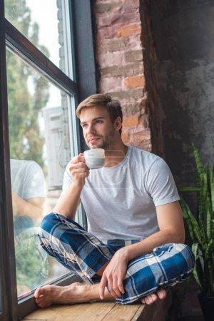 Photo pour Foyer sélectif de jeune homme assis avec une tasse de café sur le rebord de la fenêtre - image libre de droit