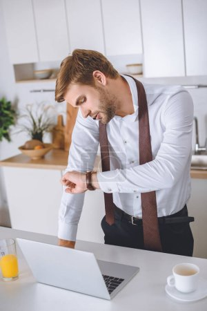 serious businessman talking on smartphone and looking at wristwatch near kitchen table with laptop and coffee cup